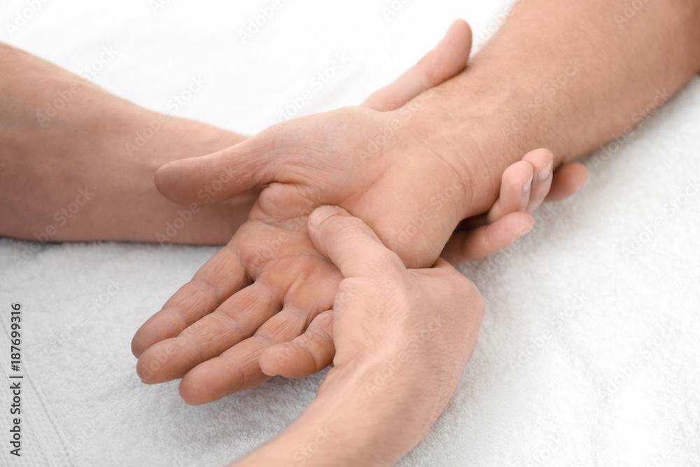Fototapeta Physiotherapist giving hand massage to senior patient, closeup