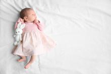 Cute Newborn Baby Girl Lying On Bed