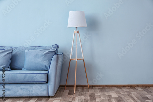 Vászonkép  Blue couch and floor lamp near color wall