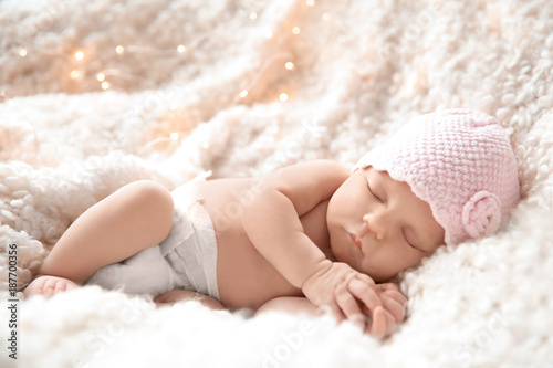Cute newborn baby girl lying on plaid