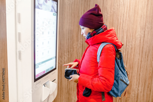 Fotografía  A woman orders meal in the touch screen terminal in the electronic menu in the f
