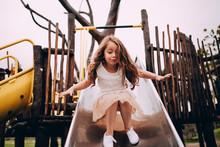 Little Caucasian Girl Having Fun On Slide On Playground