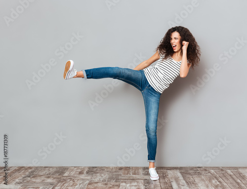 Photo  Portrait of strong young female with curly brown hair kicking invisible opponent