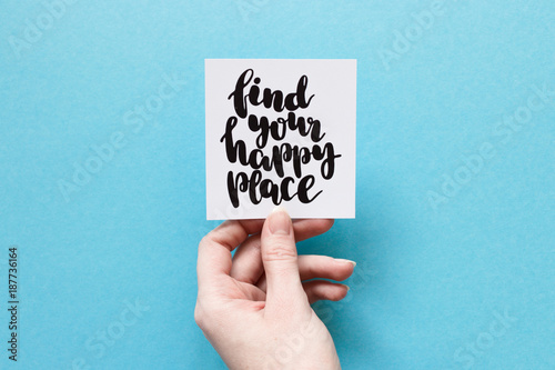 Fotografía  Minimal composition on a blue background with girl's hand holding card with quot