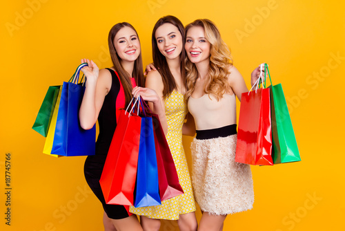 Fotografija  Three pretty, charming, successful girls in dresses holding colorful shopping ba