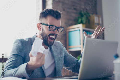 Fotografía  Close up of frustrated brunet bearded stylish entrepreneur in grey jacket, trendy specs, yelling at his laptop in office and cramps the documents