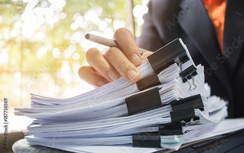 Cuadros en Lienzo Businessman hands working in Stacks of paper files for searching information on