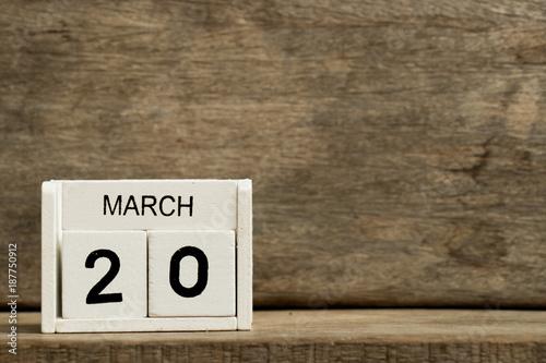 Fényképezés  White block calendar present date 20 and month March on wood background