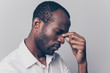 Side profile close up view portrait of nervous stressed depressed unsatisfied hard-working african man with closed eyes touching nose-bridgt trying to concentrate isolated on gray background