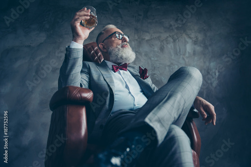 Fényképezés  Bottom view of attractive, old investor in spectacles, hold glass with brandy, i