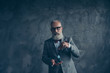 canvas print picture - Venturesome, gambling, thoughtful, brutal, old millionaire in glasses hold, show, play with casino chips, ready for poker, standing over gray background, fun, leisure, winner, win