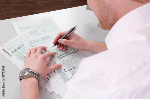 Fototapeta Junger Mann sitzt am Schreibtisch und füllt eine Steuererklärung aus