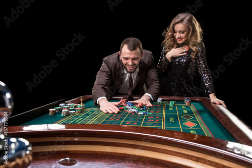 Man with woman playing roulette at the casino. Addiction to the плакат