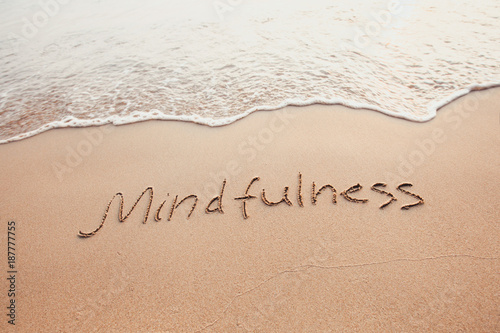 Photo mindfulness concept, mindful living, text written on the sand of beach