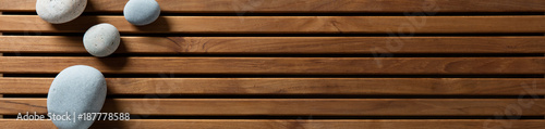 zen pebbles set on design wooden board, top view banner