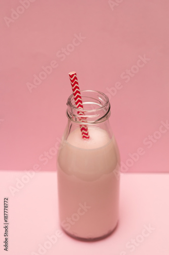 Foto op Canvas Milkshake pink strawberry milk shake in a bottle with a cocktail straw on a pink background