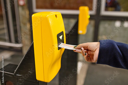 Woman punching ticket in validating machine device to entering at metro station in Prague