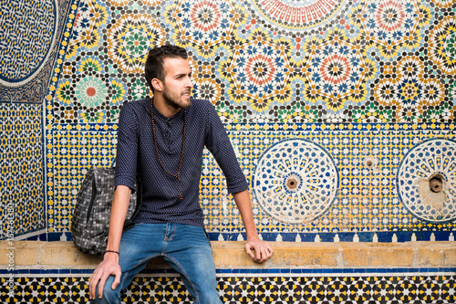 Young Muslim man sitting with traditional Moroccan decoration in background