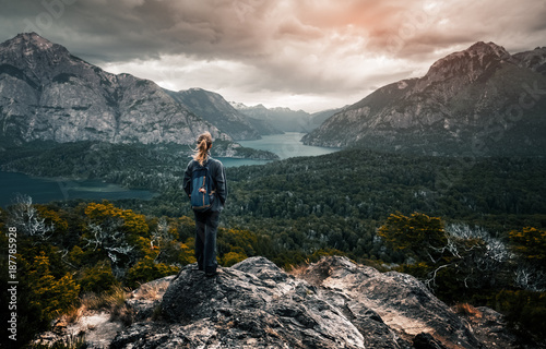 Fototapeta Woman hiker stands and enjoys valley view from viewpoint. Hiker reached top of the mountain and watching sunset. Patagonia, Argentina obraz