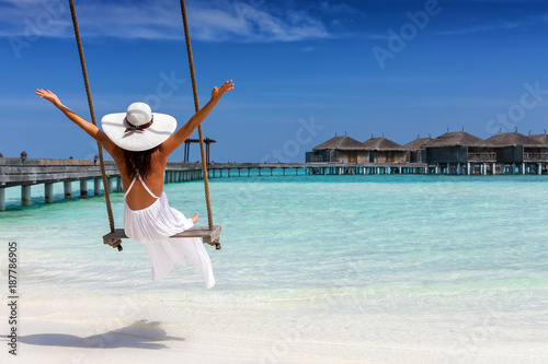 Fotografiet Attraktive Frau im weißen Kleid genießt ihren Sommerurlaub am tropischen Strand