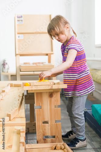 Fototapeta  girl   playing  with wooden puzzle. obraz na płótnie