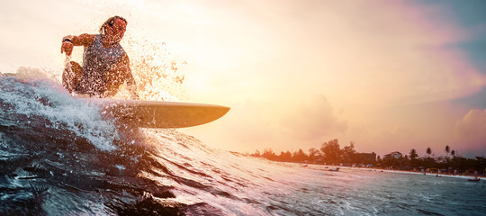 Fototapeta Surfer rides the ocean wave during sunset. Extreme sport and active lifestyle concept