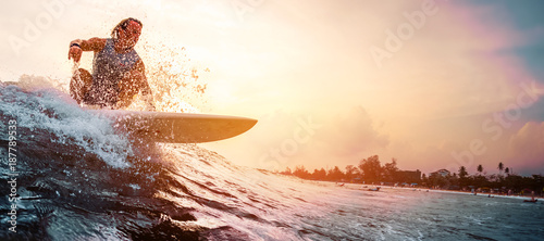 Foto Surfer rides the ocean wave during sunset