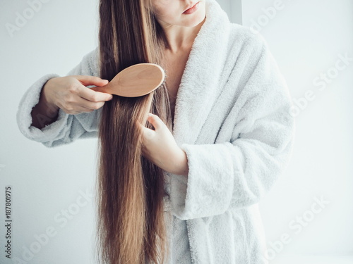 Fotografia Cute, young woman in a soft, terry dressing gown, combing her hair after Spa Ser