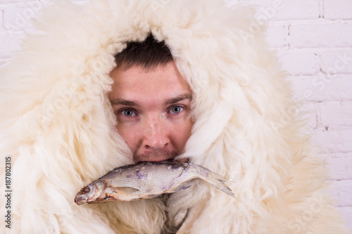 Photo  a guy in a white skin with fish in his mouth