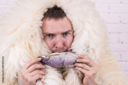 Photo  guy in a white skin with fish in his mouth on a white background