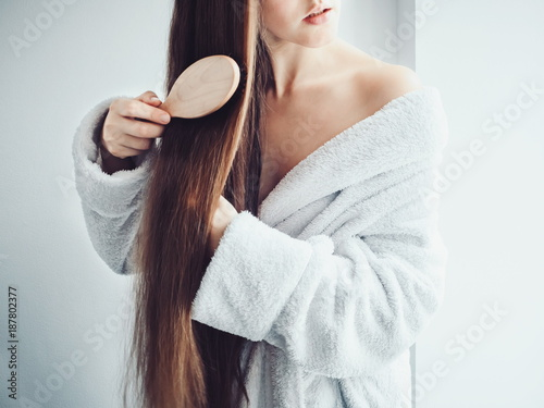 Cute, young woman in a soft, terry dressing gown, combing her hair after Spa Ser Fotobehang