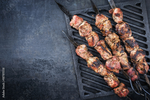 Fotomural  Traditional Russian shashlik on a barbecue skewer as top view on grillage with c