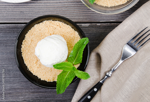 Printed kitchen splashbacks Dairy products Top view close up Apple crumble dessert with vanilla ice cream, green mint on grey wooden table. Knife on tablecloth with cake