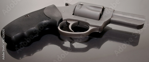 Valokuva A 44spl stainless steel revolver with a black handle laying upon a glass surface