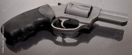 A 44spl stainless steel revolver with a black handle laying upon a glass surface Tapéta, Fotótapéta