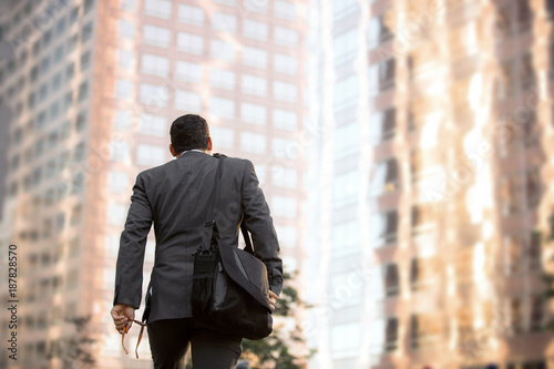 Cuadros en Lienzo Business man walking to work, motivational conceptual perspective from behind wi