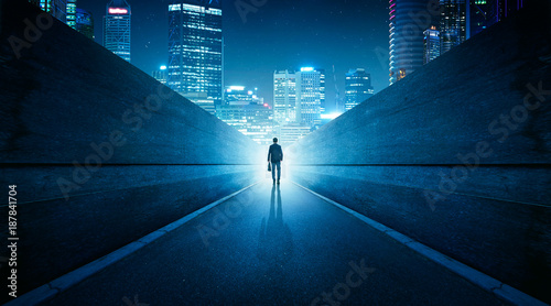 Valokuva  Ambitions concept with businessman walking from alley to modern city