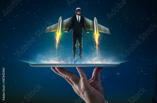 Fotografie, Obraz  Waiter hand holding an empty digital tablet with Businessman wear a rocket suit to lift , Business success concept