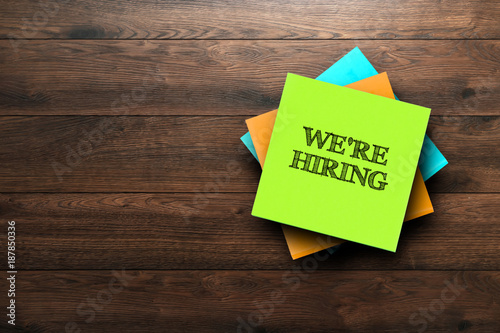 Fotografía  We're Hiring, the phrase is written on multi-colored stickers, on a brown wooden background