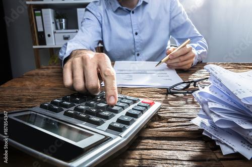 Obraz Businessperson Calculating Invoice With Calculator - fototapety do salonu