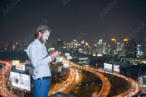 Photo  Western businessman using phone with city  background, technology communication