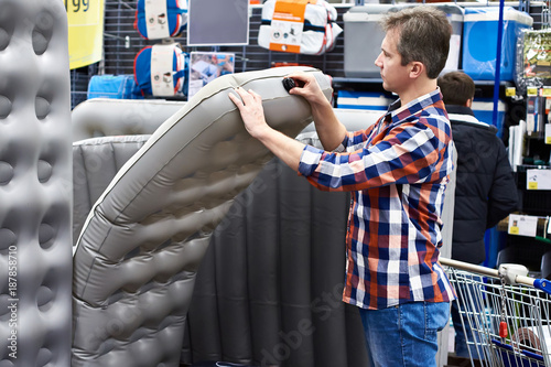 Foto  Man chooses inflatable tourist sleeping pad in sports shop