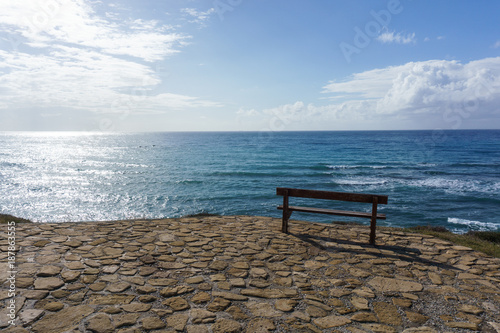Image of bench on background of sea