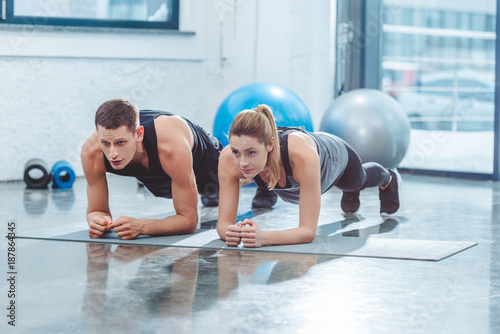 Fotografie, Obraz  sporty young couple doing plank exercise in gym