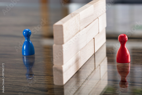 Fotografía  Red And Blue Figurine Paw Separated By Wooden Blocks