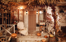 Beautiful Cozy Wooden Porch Of The House With Chair And Pumpkins In Autumn Time. Halloween Design Courtyard, Lit By Flashlights, With Dry Fall Leaves.