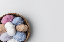 Top View Of Colored Yarn Balls In Wicker Basket On White Background