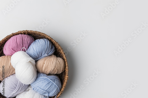 Fototapeta top view of colored yarn balls in wicker basket on white background
