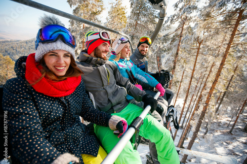 obraz dibond Smiling friends skiers and snowboarders on ski lift