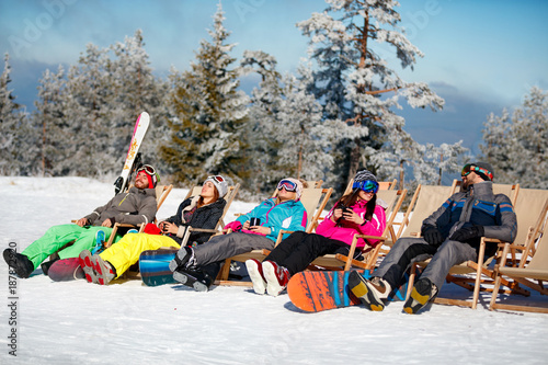 Photo sur Aluminium Glisse hiver friends sitting with deck chairs in winter mountains. Sunbathing in snow